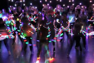 People dancing in dark room with brightly coloured glow sticks as part of glow stick fitness class