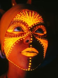 Woman's face with orange UV henna paint design