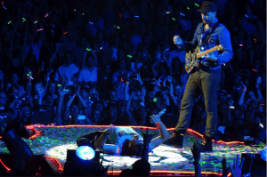 Coldplay performing in front of crowd with festival light sticks