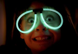 child wearing green glow stick glasses - are glow sticks for sensory play