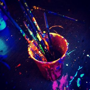 pot of UV body paint and paintbrushes