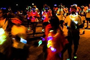runners in glow sticks and UV body paint at glow run fundraiser